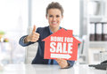 Happy realtor woman showing home for sale sign and thumbs up Stock Photography