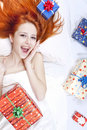 Happy red-haired girl in bed with Christmas gifts. Royalty Free Stock Photography
