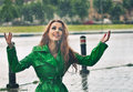 Happy redhead enjoying the rain drops in the park beautiful woman bright green coat posing outdoor shot beautiful Royalty Free Stock Photography