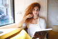Happy redhead young lady sitting in cafe while reading magazine Royalty Free Stock Photo