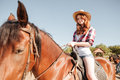 Happy redhead young woman cowgirl smiling and riding horse Royalty Free Stock Photo