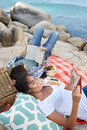 Happy and relaxed couple reading during a picnic on the rocks n enjoying near ocean book Stock Image