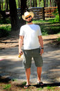 Happy relaxed cowboy a relaxing day off for a standing wearing a white straw western hat shorts and flip flops drink in hand with Royalty Free Stock Photo
