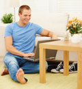 Happy relaxed guy using a laptop at home Royalty Free Stock Photos