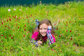 Happy relaxed kid girl on a spring flowers meadow smiling with green grass Royalty Free Stock Photo