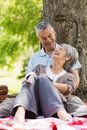 Happy relaxed senior couple sitting at park women and men the Royalty Free Stock Photos