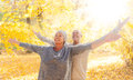 Happy retirement autumn couple with outstreched arms Stock Images