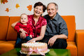Happy retirement first birthday of grandchild grandparents with their small celebrating at home Stock Photography