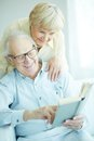 Happy retirement portrait of a candid senior couple reading book together Stock Images