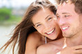 Happy romantic couple on beach in love portrait of joyful young multi ethnic young embracing each other having fun outdoors Royalty Free Stock Image