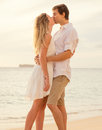 Happy romantic couple on the beach at sunset embracing each other man and women in love watching sun set into ocean Royalty Free Stock Photo