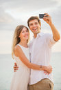 Happy romantic couple on the beach taking photo of themselves with smart phone at sunset man and women in love Stock Photo