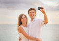 Happy romantic couple on the beach taking photo of themselves with smart phone at sunset man and women in love Royalty Free Stock Image