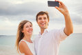 Happy romantic couple on the beach taking photo of themselves with smart phone at sunset man and women in love Royalty Free Stock Images