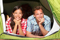 Happy romantic couple camping in tent looking forest campers smiling outdoors forest relaxing multiracial Stock Photo