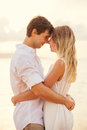 Happy romantic couple having loving moment touching foreheads looking into eachothers eyes man and women in love on the beach at Royalty Free Stock Photos