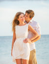 Happy romantic couple kissing on the beach at sunset man and women in love Stock Photography