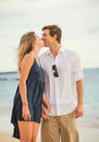 Happy romantic couple kissing on the beach at sunset man and women in love Stock Photo
