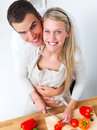 Happy romantic couple preparing food in kitchen Stock Photography