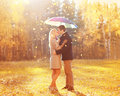 Happy romantic kissing couple in love with colorful umbrella together at warm sunny day over yellow flying leafs Royalty Free Stock Photo