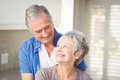 Happy romantic senior couple looking at each other in home Stock Photography