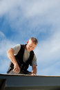 Happy roofer working on the rooftop under the sun Royalty Free Stock Photo