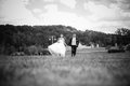 Happy run black and white photo of newly married couple running on field Stock Photo