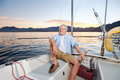 Happy sailing man boat carefree portrait of mature retired on ocean at sunrise Royalty Free Stock Image