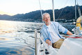 Happy sailing man boat carefree portrait of mature retired on ocean at sunrise Royalty Free Stock Photos