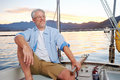 Happy sailing man boat carefree portrait of mature retired on ocean at sunrise Stock Images