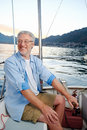 Happy sailing man boat carefree portrait of mature retired on ocean at sunrise Stock Photos