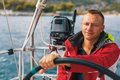 Happy sailor at the helm of his sailing yacht. Sport.