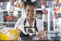 Happy saleswoman accepting payment from customer credit card in cheese shop Stock Image