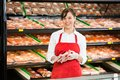 Happy saleswoman holding meat packages at counter portrait of in butcher s shop Royalty Free Stock Images