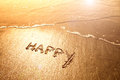 Happy sand handwriting word on sea with wave and beautiful golden sunlight with flare Royalty Free Stock Photos