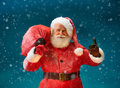 Happy Santa Claus gesturing thumb up with big bag full of gifts to children.