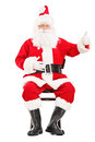 Happy santa claus sitting on a wooden chair and giving a thumb u up isolated white background Royalty Free Stock Images