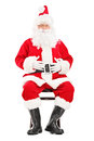 Happy santa claus sitting on a wooden chair isolated white background Stock Photography