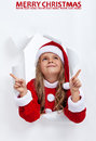 Happy santa girl at christmas pointing upwards to copy space smiling time Stock Photography