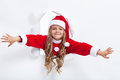 Happy santa girl opening the holidays season leaning through hole in paper layer Royalty Free Stock Images