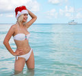 Happy santa girl on tropical beach beautiful blonde young woman in red christmas hat and bikini enjoying blue sea concept of new Royalty Free Stock Photo