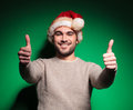 Happy santa man is making the ok gesture thumbs up on green background Royalty Free Stock Photo