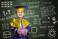Happy scholar dressed toddler with piggybank carrying a Royalty Free Stock Photography
