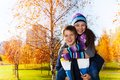 Happy school age couple and laughing and years old of kids boy an girl in warm autumn clothes in the park Stock Photos