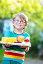 Happy school boy with books, apple and drink bottle Royalty Free Stock Photo