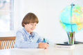 Happy school boy doing his homework at a white desk Stock Photos