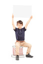 Happy school boy holding a blank panel above his head seated on pile of books isolated white background Stock Photos