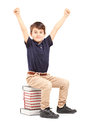 A happy school boy raised his hands gesturing happiness seated on pile of books against white background Stock Photos