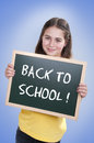 Happy school girl with chalk board student holding back to blackboard Stock Images