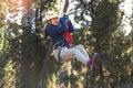 Happy school girl enjoying activity in a climbing adventure park